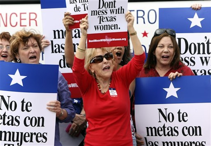 In this March 6, 2012 file photo Mary Green, Peg Armstrong and Jan Perrault hold up signs during Women's Health Express, a bus event held in San Antonio, Texas, to protest the attempt to cut Planned Parenthood out of the state's Women's Health Plan. Federal Judge Lee Yeakel ruled Monday there is sufficient evidence a law barring Planned Parenthood from participating in the Texas' Women's Health Program in unconstitutional and stopped the state from banning the organization from receiving state funds. (AP Photo/San Antonio Express-News, Helen L. Montoya, File)