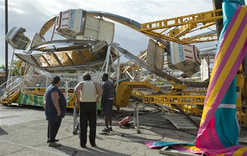 Ottaway Amusement, Inc. workers survey the damage to a 65-foot tall Ferris wheel Sunday morning, April 15, 2012, that toppled over onto another ride at Kellogg and Greenwicht following a tornado that swept through east Wichita overnight Saturday. (AP Photo/The Wichita Eagle, Mike Hutmacher)