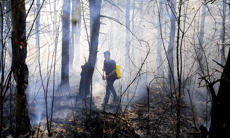 Staff photo by Andy Molloy BLAZE BUSTER: Caleb Trudeau searches for a hot spot Wednesday while extinguishing a brush fire along the Maine Turnpike in West Gardiner. Several fire companies responded to the blaze that covered the Turnpike with smoke.