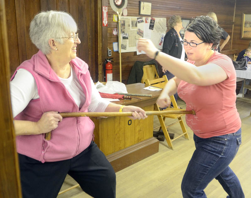 Instructor Karen Jones, owner of Tao Karate Club, right, demonstrates with Johan Brown how a cane can be used to push away an attacker during a self-defense demonstration on Saturday morning at the Chlesea Grange.