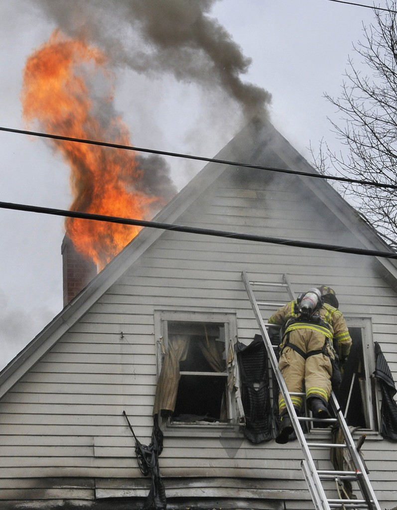 A firefighter climbs a ladder to reach the fire at 28 Raymond St. in Biddeford on Saturday morning. No one was hurt.