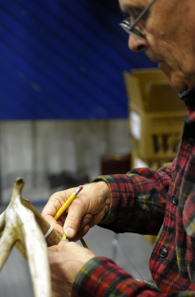 Dick Arsenault of the Maine Antler and Skull Trophy Club measures antlers.
