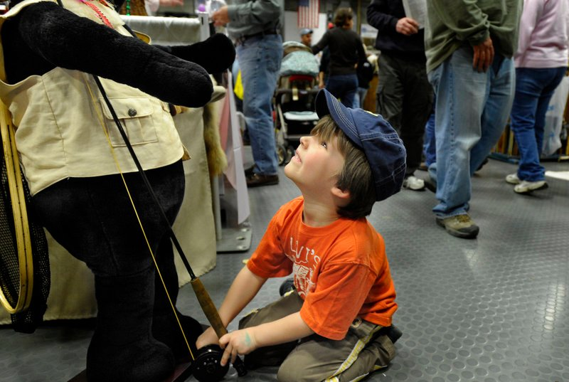 "Oblivious to the hundreds of people milling around the floor of the Augusta Civic Center, Embden Nelson, 4, of Canaan, enjoys playing with a fishing rod in the hands of ""Birdox the Bear"" at the Maine Sportsman's Show on Saturday."