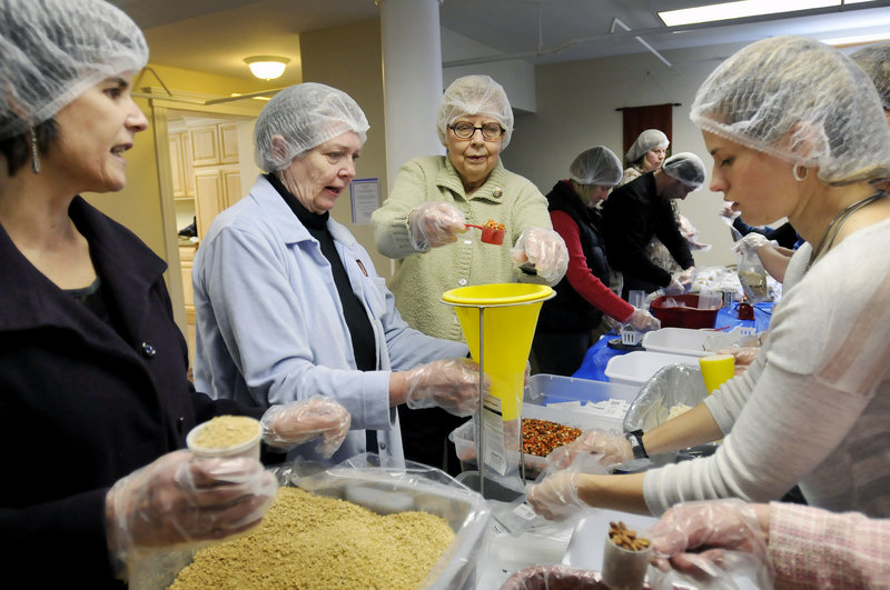 Volunteers package food assembly-line style Sunday at Trinity Lutheran Church in Westbrook, where their aim was to package 10,000 meals in about an hour as part of the Outreach Inc. Kids Care program. Volunteers, from left to right, are Janette Gustafson, Nancy Crump, Hazel Maloney and Abi Gustafson.