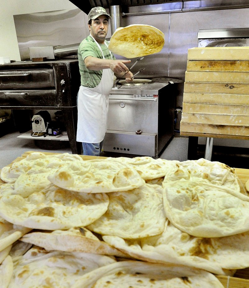 Tandoor owner Audai Naser tosses a hot flatbread from the oven on to a table to cool.