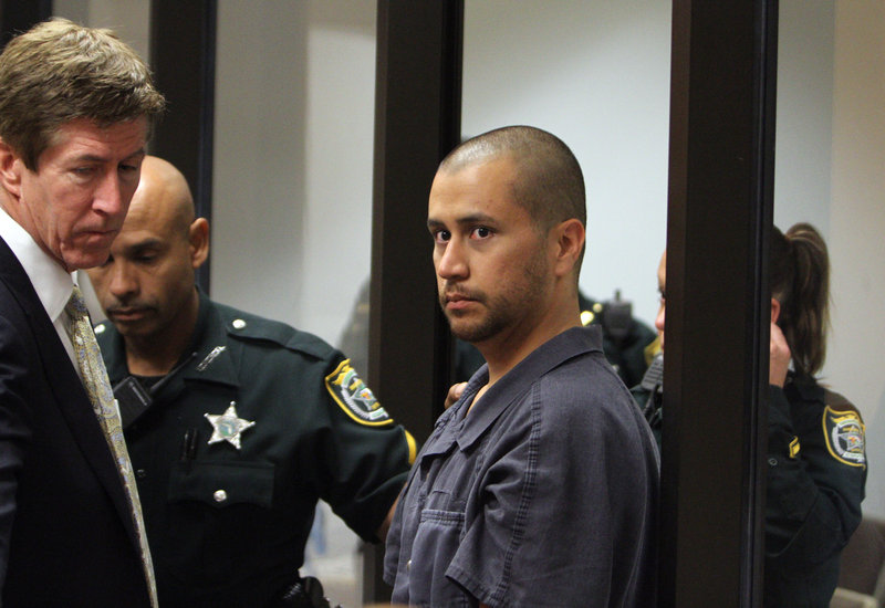 George Zimmerman is directed by a Seminole County deputy and his attorney Mark O'Mara during a court hearing Thursday in Sanford, Fla. Zimmerman has been charged with second-degree murder in the shooting death of 17-year-old Trayvon Martin.