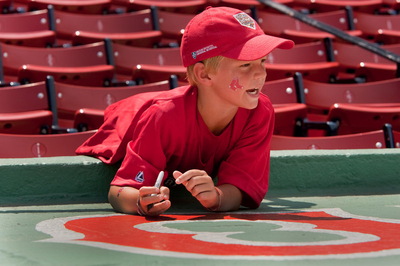 Dillon Bolduc of South Portland makes some memories by signing the top of the Sea Dogs dugout.