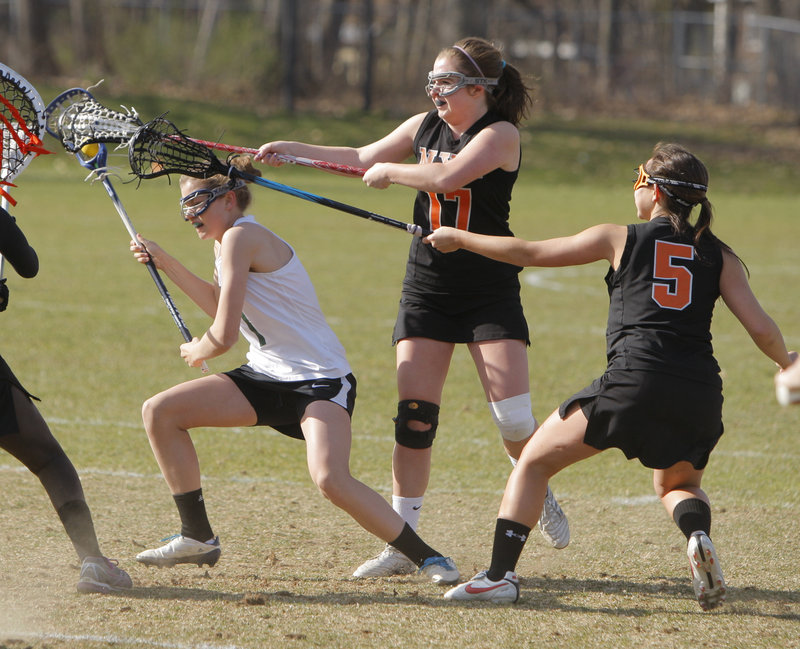 Walker Foehl, left, of Waynflete is pressured by North Yarmouth Academy's Katie Cawley, center, and Hannah Twombly. Waynflete built a 14-1 halftime lead on the way to a 15-5 win.