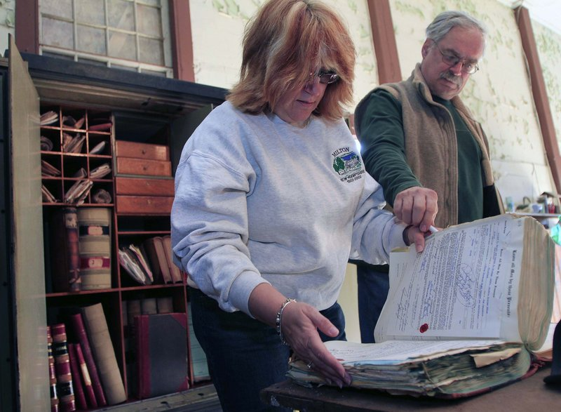 Anne Clark, town clerk and tax collector in Milton, N.H., and Town Administrator Tony Mincu look through old ledgers discovered in a long-locked town safe in the old town hall Saturday. It took a locksmith three hours to open the safe.