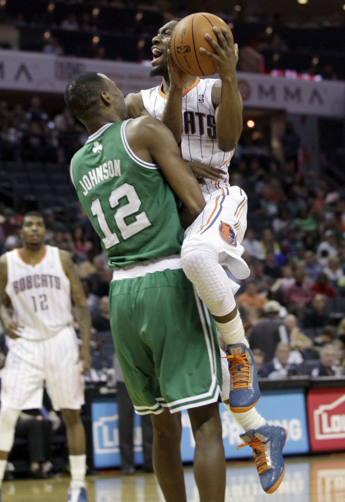JaJuan Johnson of the Celtics tries to take a charge from Charlotte's Kemba Walker during Boston's 94-82 victory Sunday night.
