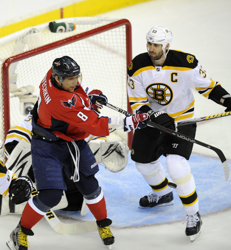 Alex Ovechkin of the Washington Capitals, left, swats at the puck as defenseman Zdeno Chara of the Boston Bruins closes in Monday night. Chara scored the winner in a 4-3 victory.