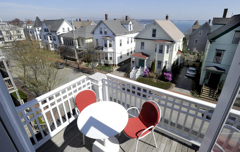 The third-floor balcony of the triple-decker on Munjoy Hill in Portland owned by Pamela Hawkes and Scott Teas boasts views of Casco Bay.