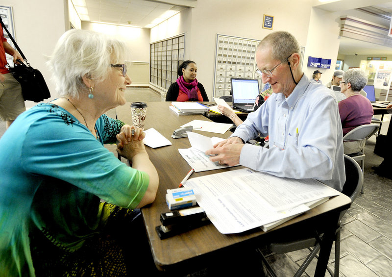 R.J. Harper, right, an IRS-certified volunteer tax preparer, assists last-minute filer Ana Dana from South Portland at a desk set up Tuesday afternoon in the lobby of the Forest Avenue post office.