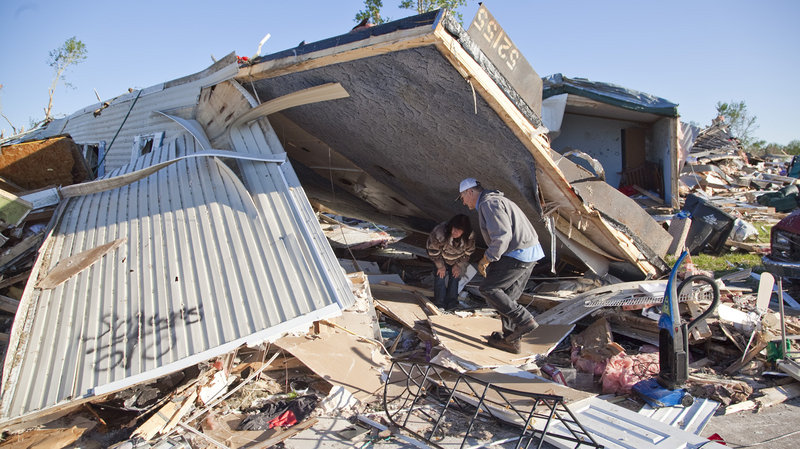 Richard Keith helps sister-in-law Mitzi Keith with salvage and cleanup work Tuesday in Pinaire Mobile Home Park after a tornado swept through the Oaklawn neighborhood in southeast Wichita, Kans., on April 14.
