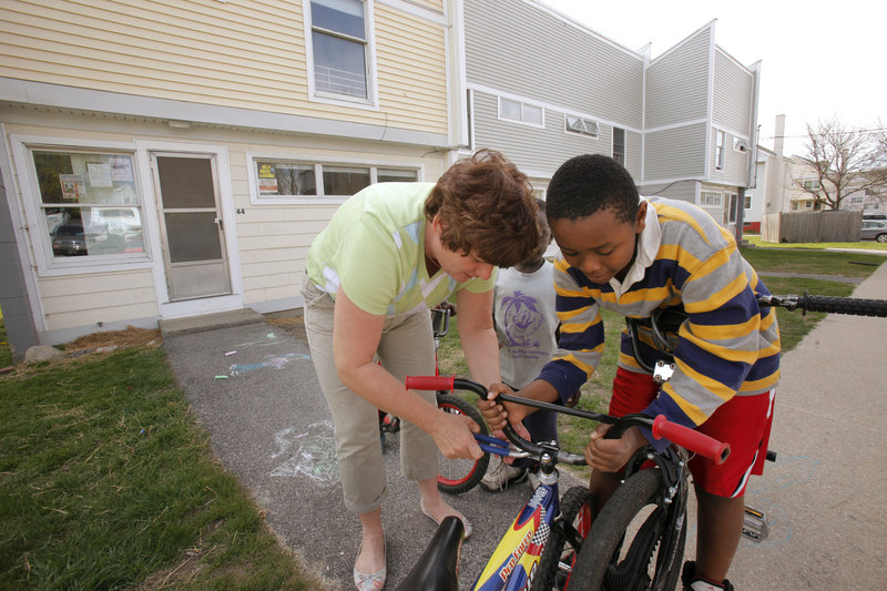 Services coordinator Janine Kaserman fixes a bike Wednesday for Yousef Zakaria outside the Community Policing Center in the Kennedy Park neighborhood. Kaserman is now splitting her time between the Mayo Street center and one on Munjoy Hill because of a staff vacancy.
