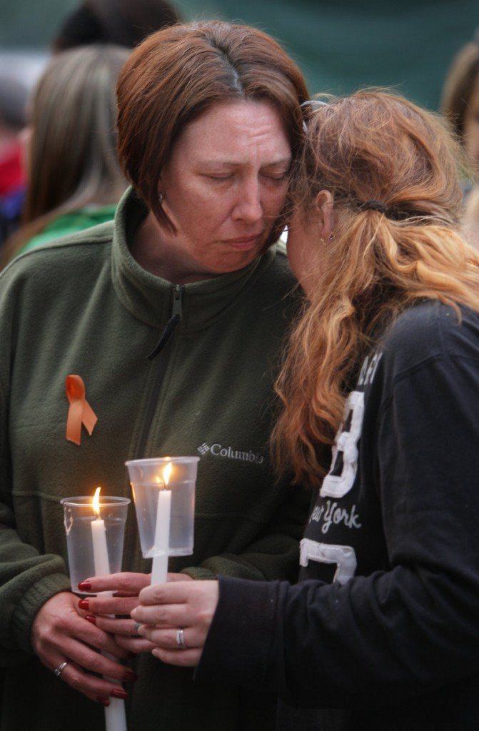 Valerie Page, wife of Sean Page, is comforted by a friend during a candlelight memorial at her home in Biddeford on Wednesday night. About 100 people attended the event.