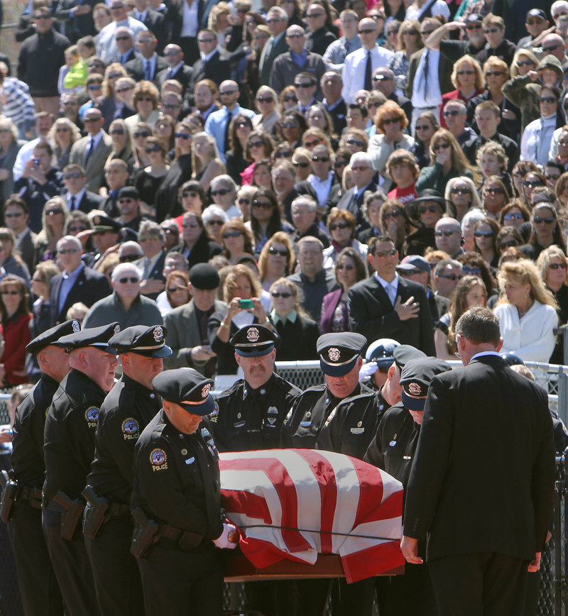 Thousands of mourners watch as officers from the Greenland (N.H.) Police Department carry the body of their chief, Michael Maloney, during his funeral service in Hampton, N.H., on Thursday. Maloney, 48, was fatally shot in a drug raid last week; four other officers who were wounded in the raid were in attendance at the ceremony.
