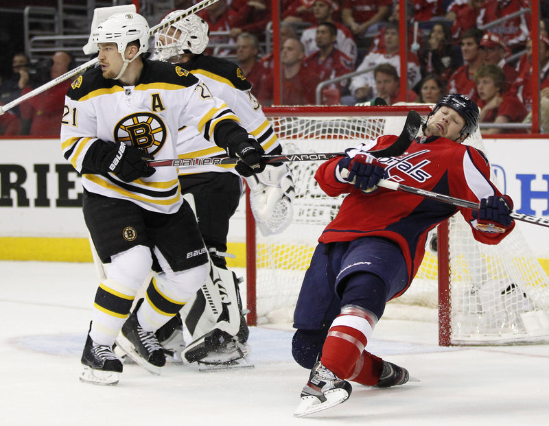 Matt Hendricks of the Washington Capitals heads to the ice Thursday night after taking a stick from Andrew Ference of the Boston Bruins during the second period of their playoff game. The Capitals won 2-1 to even the best-of-seven series at two games each.