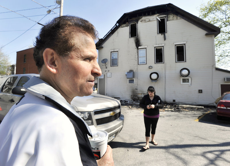 Owner Angelo Sotiropoulos surveys the damage to the downtown building housing the Gorham House of Pizza on Friday.