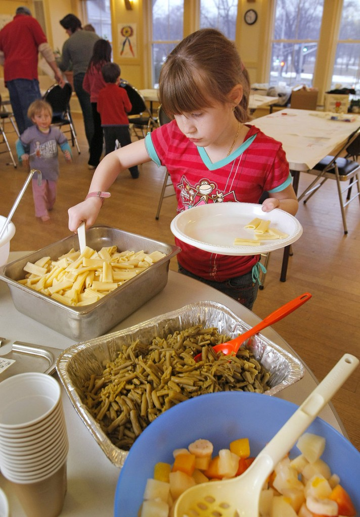 Jenna Buzzell scoops pasta onto her plate in 2008 at the weekly Parkside Supper Club, a dinner program, held at Portland's Parkside Community Center, designed to help build community. This is a good time of year to begin to forge closer bonds with people who live in the neighborhood, a reader says.