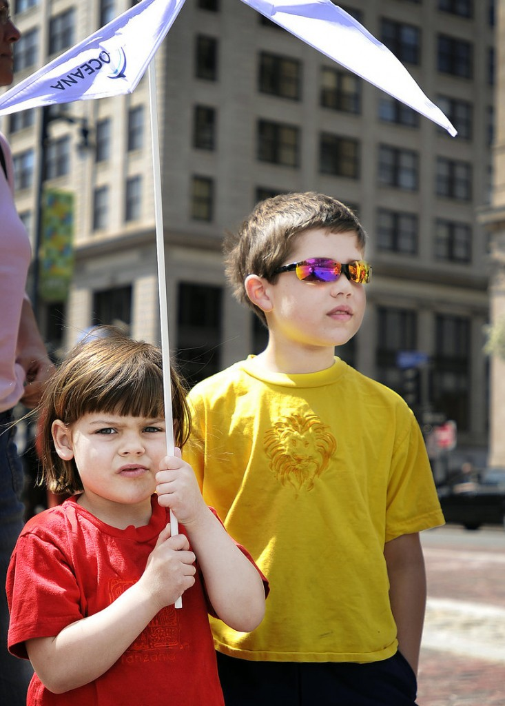Millie Peterson, 5, of Portland hoists a windspinner above her head as she and her brother, Cooper, 7, take in a mock oil spill and wind farm demonstration in Monument Square.