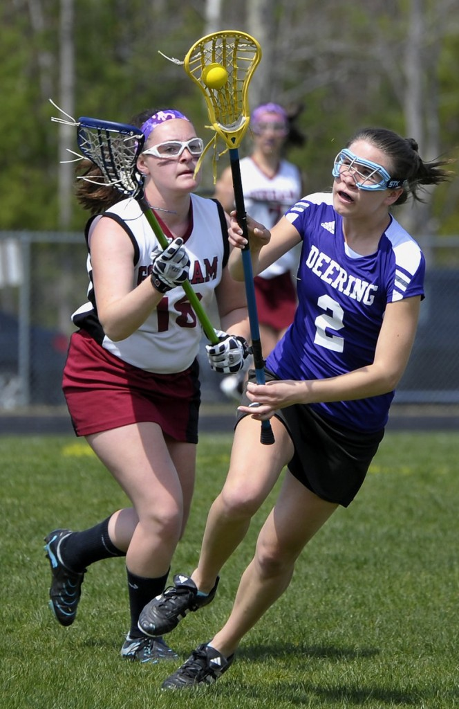 Delaney Loring, right, of Deering attempts to keep the ball in the basket as Ashley Gaudette of Gorham looks to knock it out during the first half.