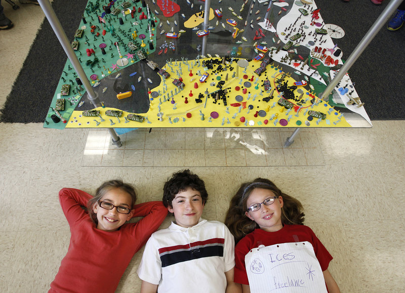 Kaitlyn Gallaway, left, Samuel Knotts, and Sarah Schmidt, fourth-graders at Agnor-Hurt Elementary School in Charlottesville, Va., are shown with the World Peace Game.