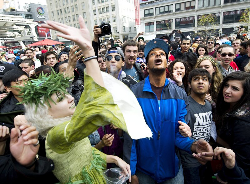 "The ""Weed Fairy,"" whose name was not available, throws marijuana joints to the crowd as thousands take part in the annual marijuana 4/20 smoke-off at Dundas Square in Toronto on Friday."