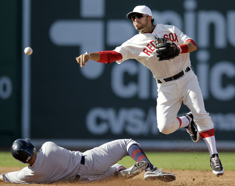 Mike Aviles of the Red Sox turns a double play over New York's Nick Swisher. Both teams wore throwback uniforms with no numbers on Fenway Park's 100th anniversary.