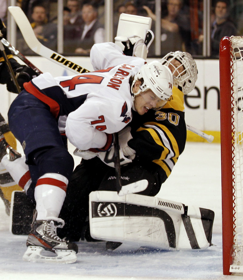 John Carlson of the Caps slams into Bruins goalie Tim Thomas in Saturday's game at Boston. Carlson received a penalty on the play.