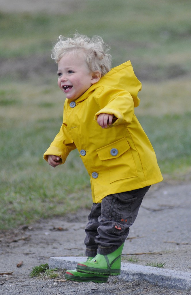 Jasper Forgit, 1, of Portland jumps with his raincoat and boots on as he walks with his grandmother, Mary Ann Forgit, near East End Beach in Portland on Sunday.