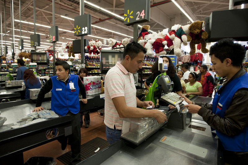 A man pays at the cash register at a Walmart Superstore in Mexico City. Walmart Stores Inc. hushed up a vast bribery campaign that top executives of its Mexican subsidiary carried out to build stores across Mexico, according to The New York Times.