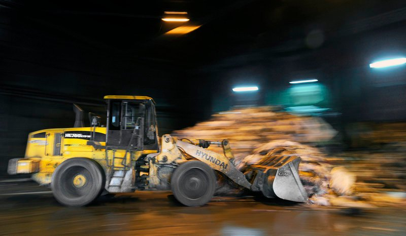 """A bucket loader moves trash Monday into """"the bunker"""" at ecomaine's processing facility in Portland. The plant, which opened in 1988, is owned and operated by 21 southern Maine communities."""