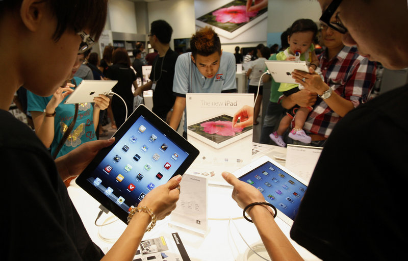 Shoppers look at new iPad tablet computers at an Apple store in Klang, Malaysia. Apple is set to report another record quarterly profit today.