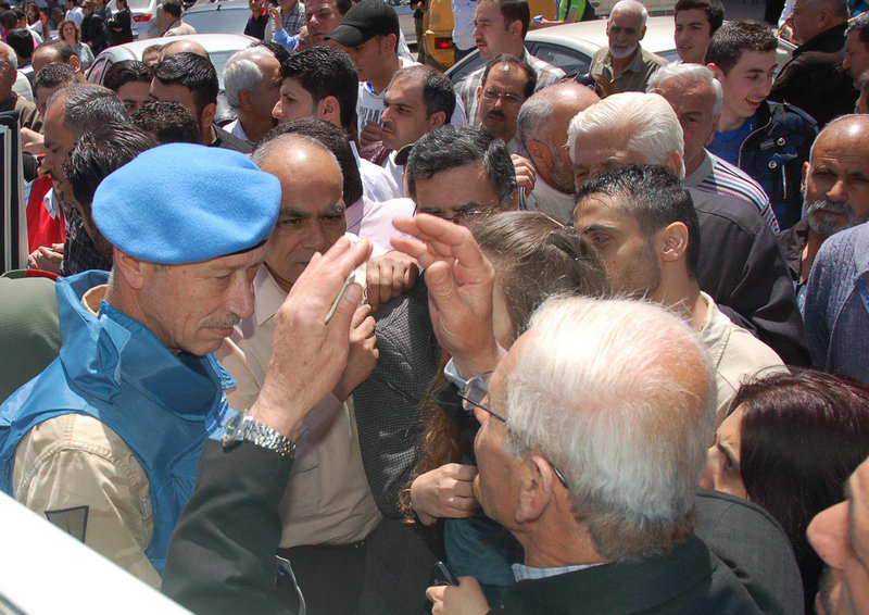 A U.N. observer, left, speaks with Syrian citizens during the monitors' visit to pro-Syrian regime neighborhoods in Homs province, central Syria, on Monday.
