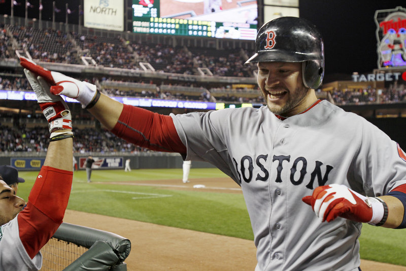 Cody Ross returns to the dugout after tying the game with a two-run homer in the seventh inning Monday. Ross also homered in the ninth to give the Red Sox a 6-5 win.