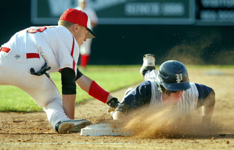 Nick Volger of Portland gets a face full of dirt Tuesday while making it back to first base ahead of a tag by Sam Wessel of Scarborough during their game at Hadlock Field. Scarborough came away with a 5-3 victory.
