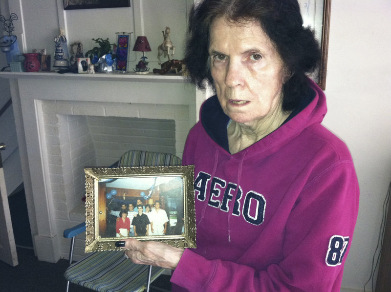 """""""I'm coping as best I can,"""" said Carol Swenson, the mother of slaying suspect Michael Swenson. She holds a family photo in her Scarborough home Wednesday. """"I'm very upset and hope it wasn't true,"""" she said after her son's arrest."""