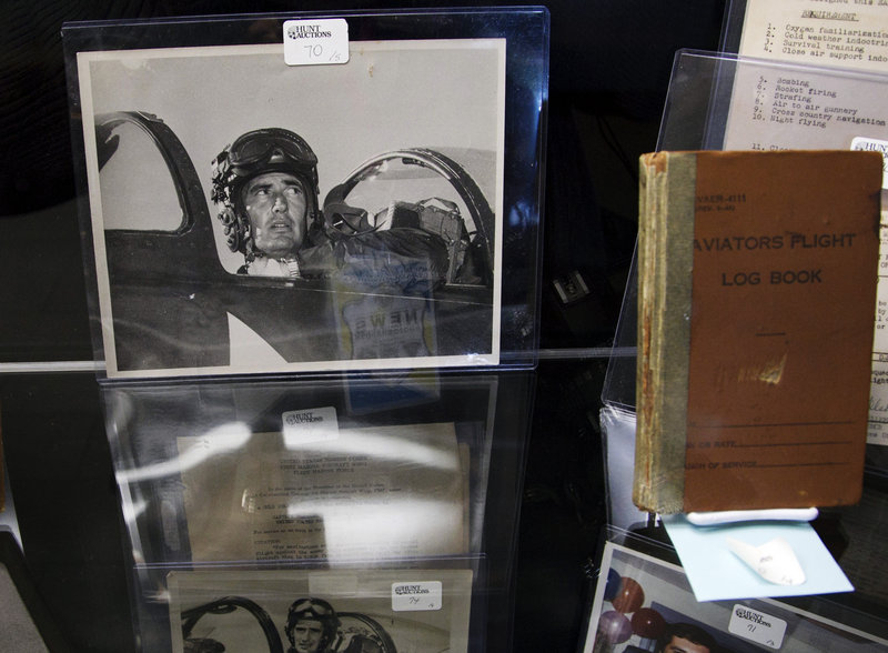 A Korean War-era photograph of Ted Williams sits in a display case next to a 1952-1953 flight log book during the auction preview Wednesday at Fenway Park. Fans will be able to see hundreds of items during the preview, which will last through Friday. The auction is Saturday.