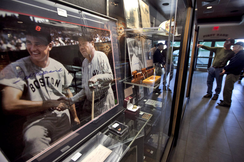 A 1943 photograph to be auctioned Saturday shows Red Sox legend Ted Williams shaking hands with the Yankees' Babe Ruth. The photo was in a display case at Fenway Park during a preview of items once owned by Williams.