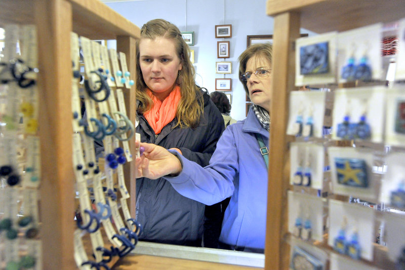 Cash mob participants Katie Lybrand, left, and her mom, Karen, look over some earrings at Lisa-Marie's Made in Maine, a shop on Exchange Street in Portland, on Thursday evening. The social-media-driven cash-mob events are designed to promote patronage at local businesses.