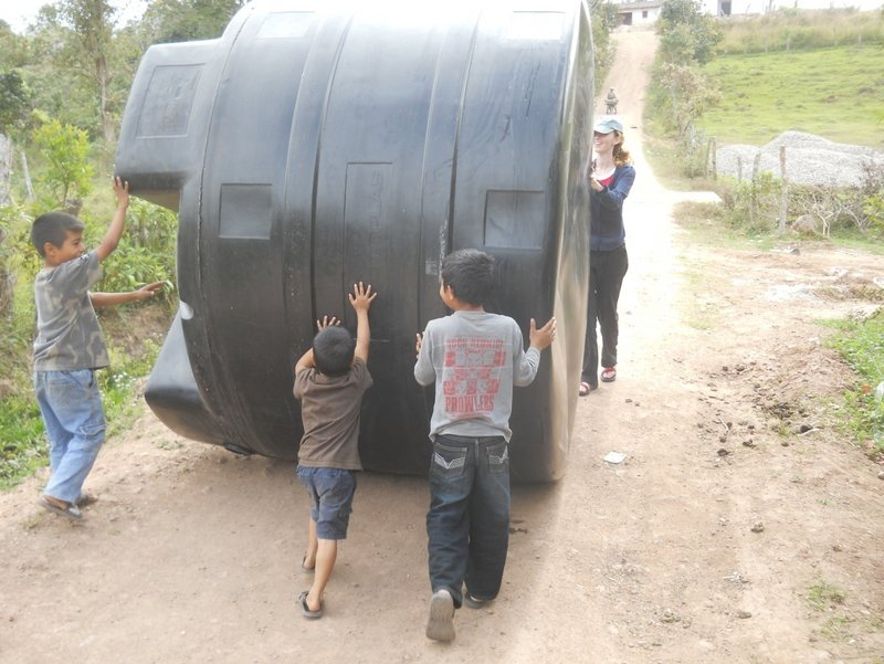 Honduran youths roll one of five septic tanks for a massive wastewater system designed and built by the UMaine chapter of Engineers Without Borders.