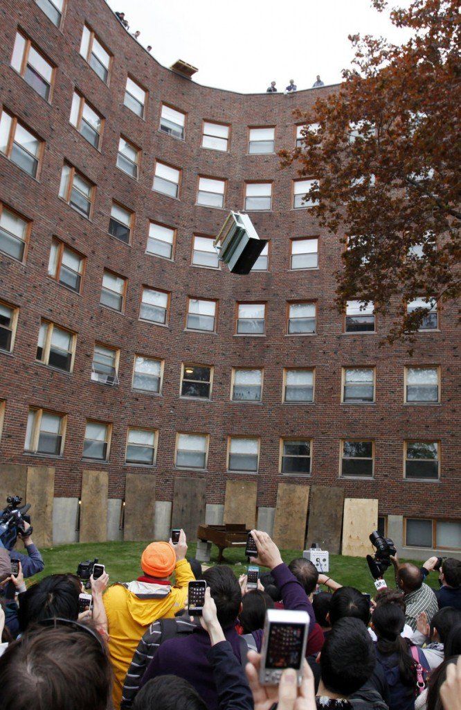 A crowd watches as an upright piano falls from the roof of the Baker House dormitory onto a second piano, a baby grand, at the Massachusetts Institute of Technology in Cambridge, Mass., on Thursday.