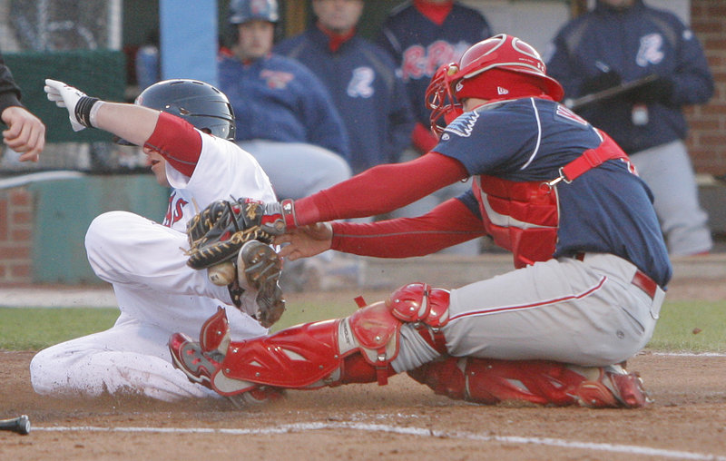 Bryce Brentz, left, of the Sea Dogs scores one of his two runs as Reading catcher Sebastian Valle drops the ball during the fourth inning Friday night in Portland.