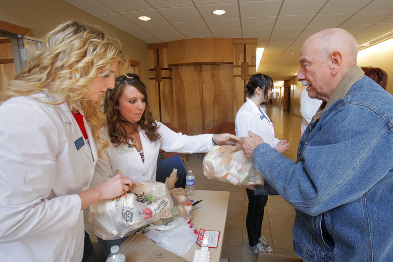 Lindsey Cashell, left, and Erika Newman, students at the University of New England College of Pharmacy, accept and log bags of medication from Art Wood of Portland on Saturday. The take-back program was part of a National Prescription Drug Take-Back Day, which allows people to dispose of unwanted or expired prescription and over-the-counter medications.