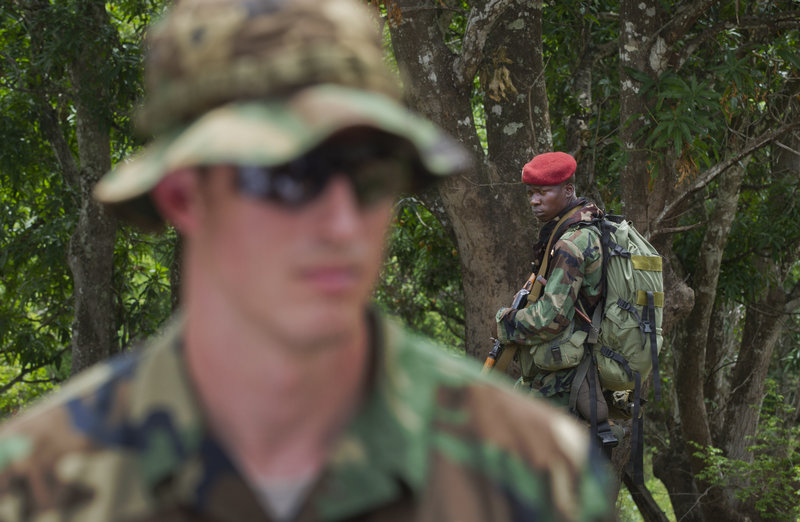 A soldier from the Central African Republic, right, looks across as U.S. Army special forces Capt. Gregory, 29, left, who would give only his first name in accordance with security guidelines, speaks Sunday with other troops from the Central African Republic and Uganda, where they're searching for warlord Joseph Kony, in Obo, Central African Republic.