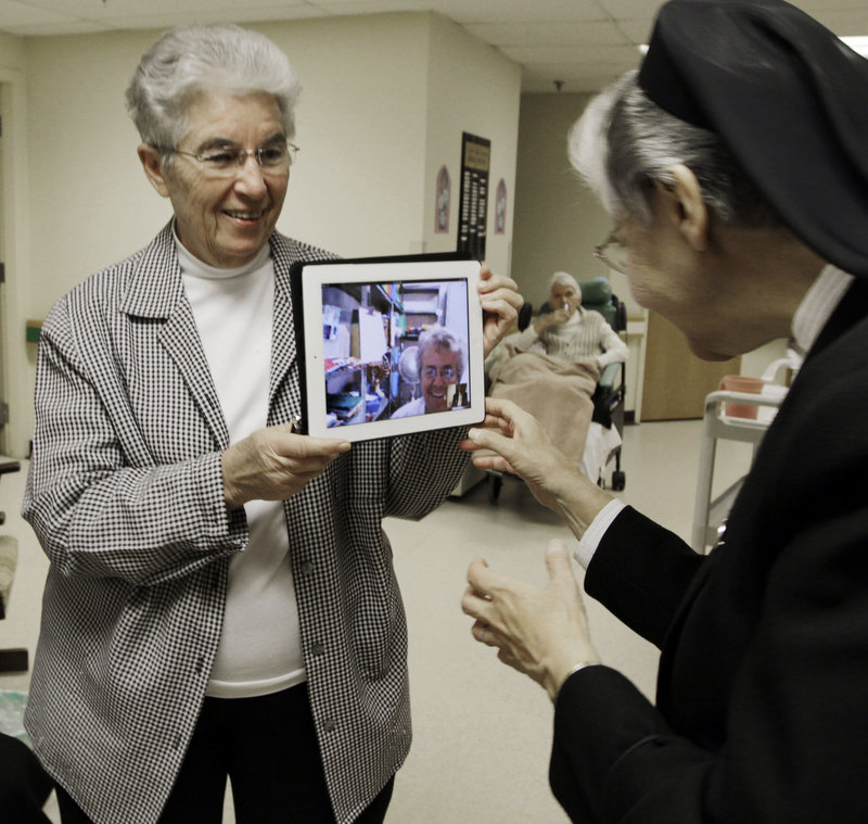 Priscille Roy, left, shows Sister Elaine Lachance an iPad with the image of a colleague who is in Brazil, Sister Pauline Demers, at St. Joseph Convent in Biddeford.