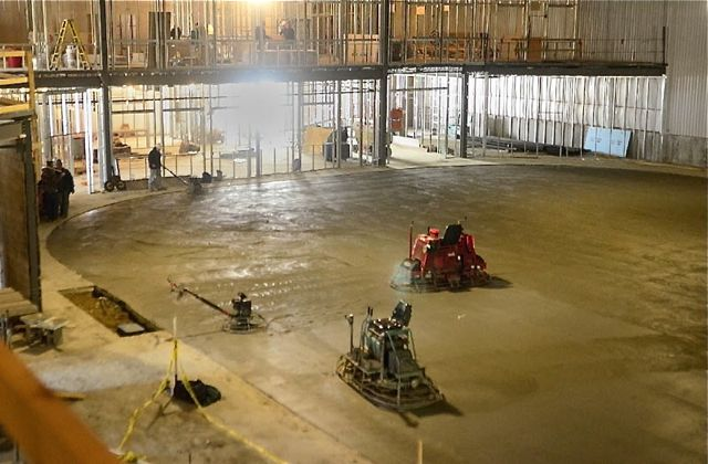 A worker on Wednesday finishes the concrete floor that will be under the ice rink at the new Bank of Maine Ice Vault in Hallowell. The refrigeration pipes are under the 260 yards of concrete and will take 28 days to cure, according to rink manager K.C. Johnson. He said that they plan to have ice by June 1.