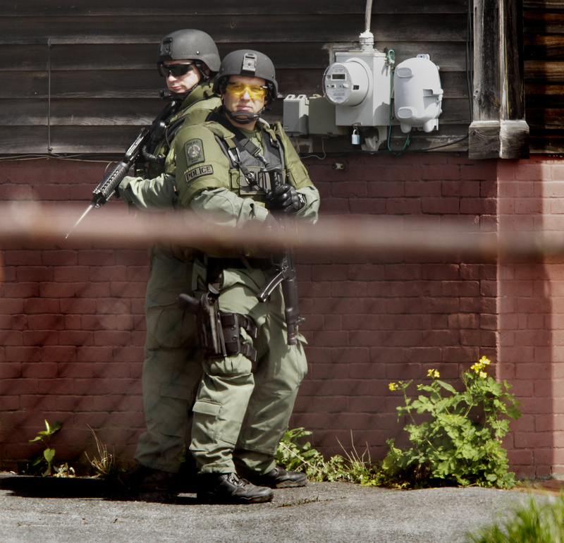 Heavily armed members of Portland Police's Special Reaction Team position themselves on Cedar Street while trying to apprehend shooting suspect Brian Kelley in Portland on Saturday.