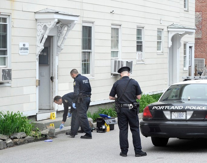 Portland police officers investigate the scene of a stabbing earlier today at 9 Cedar St. in Portland.